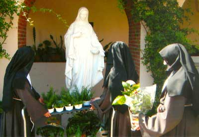 Nuns planting near Mary statue