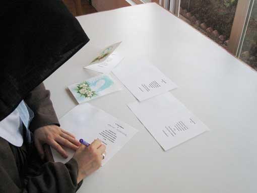 Nun writing a prayer card